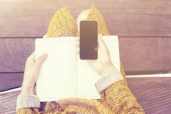 女孩坐与空白的日志和智能手机的长木凳 免版税库存图片