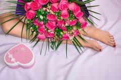 女孩坐与花桃红色花束的一张床  一件礼物为假日 免版税库存图片