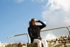 女孩坐举她的手的岩石对眼睛,在期望 免版税库存照片