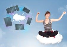 女孩坐享受云彩网络服务的云彩 图库摄影