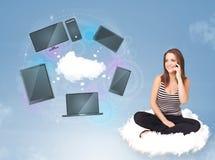 女孩坐享受云彩网络服务的云彩 免版税库存图片