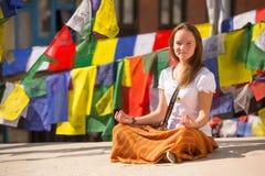 女孩坐佛教stupa 免版税库存图片