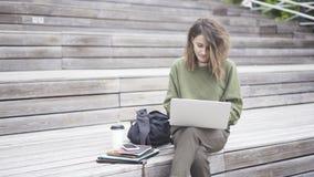 女孩坐台阶与膝上型计算机一起使用 库存图片