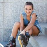 女孩坐台阶和放置冰鞋 免版税库存图片