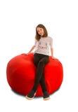女孩坐圆形红色装豆子小布袋椅子 库存照片