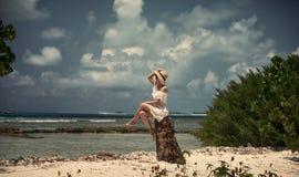 女孩坐在一个白色礼服和帽子的一个树桩 海洋的岸 马尔代夫 热带 假期 海岛 库存照片