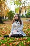 女孩坐在一秋天天的地面 免版税库存图片