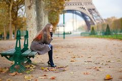 女孩坐在一秋天日的一条长凳 库存图片