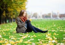 女孩坐在一秋天日的一棵草 库存照片