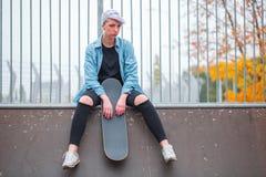 女孩坐在与一只冰鞋的一overclock顶部在她的手上 库存照片