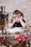 女孩坐在与俄国式茶炊的一张桌上认为 免版税图库摄影