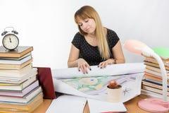 女孩坐在书桌的设计学生和疲乏部署一张大图画 免版税库存图片
