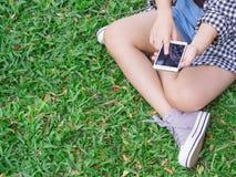 女孩坐在公园戏剧智能手机的绿草 免版税库存照片