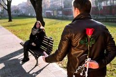 女孩坐在公园的和男朋友接近与红色玫瑰 图库摄影