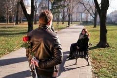 女孩坐在公园的和男朋友接近与红色玫瑰 免版税库存图片