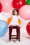 女孩坐在大五颜六色的气球背景的一把椅子  图库摄影