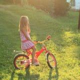 女孩坐在太阳的一辆自行车 免版税图库摄影