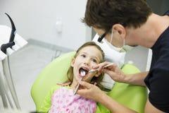 女孩坐在她的规则牙齿核对的牙齿椅子 免版税库存图片