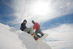 女孩坐在山坡的雪,并且人在雪板准备好去下来 库存照片