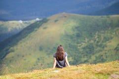 女孩坐在山边缘 库存图片