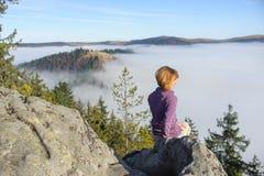 女孩坐在山顶部,看在前后 免版税库存照片