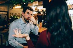 女孩坐在年轻人前面和谈话与他 他看起来乏味 人不是对交谈感兴趣  图库摄影