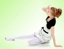 女孩坐在手边倾斜和看对sid的地板 库存图片