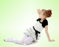 女孩坐在手边倾斜和看对sid的地板 免版税库存图片