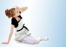 女孩坐在手边倾斜和看对sid的地板 免版税库存照片