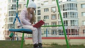女孩坐在操场的摇摆在公寓附近,使用一种计算机片剂 影视素材