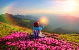女孩坐在桃红色杜鹃花中的草坪 免版税图库摄影