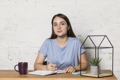 女孩坐在桌上并且直接地看 她拿着一支铅笔 在桌上值得杯 免版税库存图片