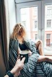 女孩坐在毯子的一个窗口 库存图片