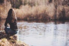 女孩坐在河森林银行的一个岩石  免版税库存图片