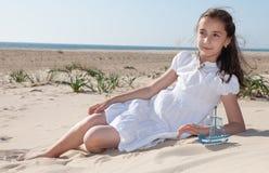女孩坐在海滩的沙子在一件白色礼服 免版税库存照片