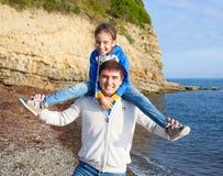 女孩坐在海背景的爸爸的肩膀 免版税库存照片