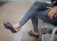 女孩坐在牛仔裤的一把椅子 免版税库存照片
