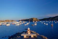 女孩坐在美丽的海湾前面的一条长凳与游艇 免版税库存照片