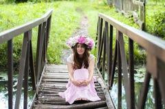 女孩坐在花花圈的一座小桥梁 图库摄影