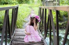 女孩坐在花花圈的一座小桥梁 免版税库存照片