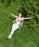 女孩坐在草甸的一把折叠椅 库存图片