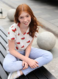 女孩坐在莲花坐的一条长凳 免版税库存照片
