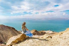 女孩坐在观看死海的峭壁的岩石在约旦 库存照片