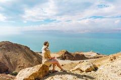 女孩坐在观看死海的峭壁的岩石在约旦 免版税库存图片