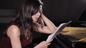 女孩坐在钢琴并且学会音乐,笔记 音乐,表现,与笔记的板料 影视素材