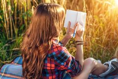 女孩坐在领域衬衣的,放松在自然,美丽的头发的麦子 在笔记本写想法 以后学生 图库摄影