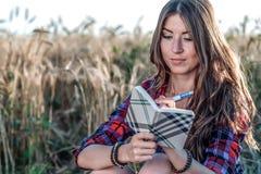 女孩坐在领域衬衣的,放松本质上,美丽的深色的头发的麦子 保持笔记薄pnany为将来 免版税库存照片