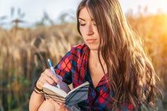 女孩坐在领域衬衣的,放松本质上,美丽的深色的头发的麦子 写想法的笔记薄 A 免版税库存图片