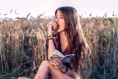 女孩坐在领域衬衣的,放松本质上,美丽的深色的头发的麦子 吃一个苹果,笔记薄pnany为 库存照片