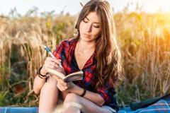女孩坐在领域衬衣的,放松本质上,美丽的深色的头发的麦子 在笔记本写想法 一名学生 免版税库存图片